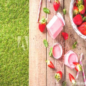 Strawberry milkshake in bottles, with fresh strawberries and mint on sunlight summer wooden and gla