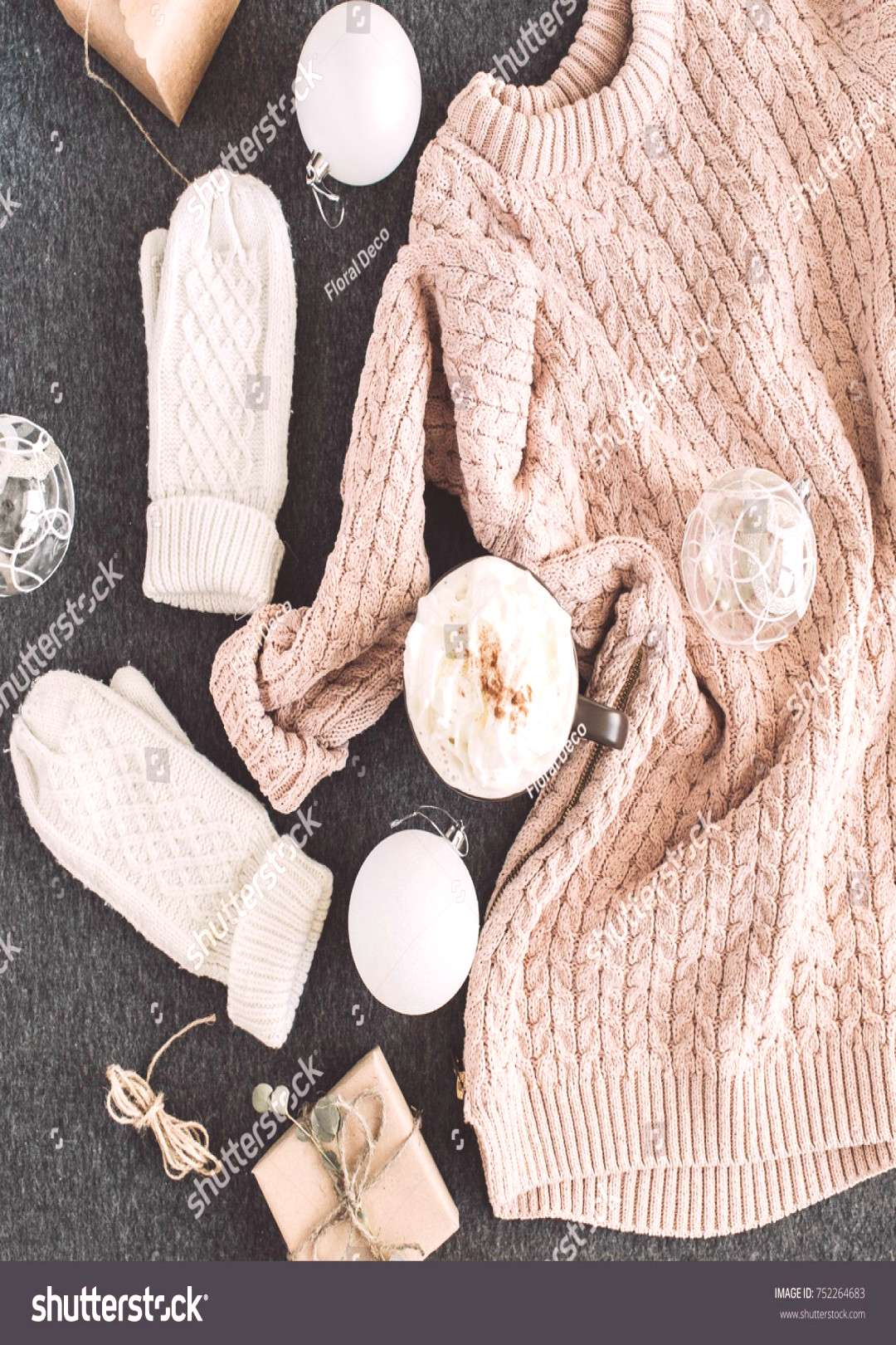 Women's winter clothes look on grey plaid. Warm beige sweater and white knitted mittens, gift box a